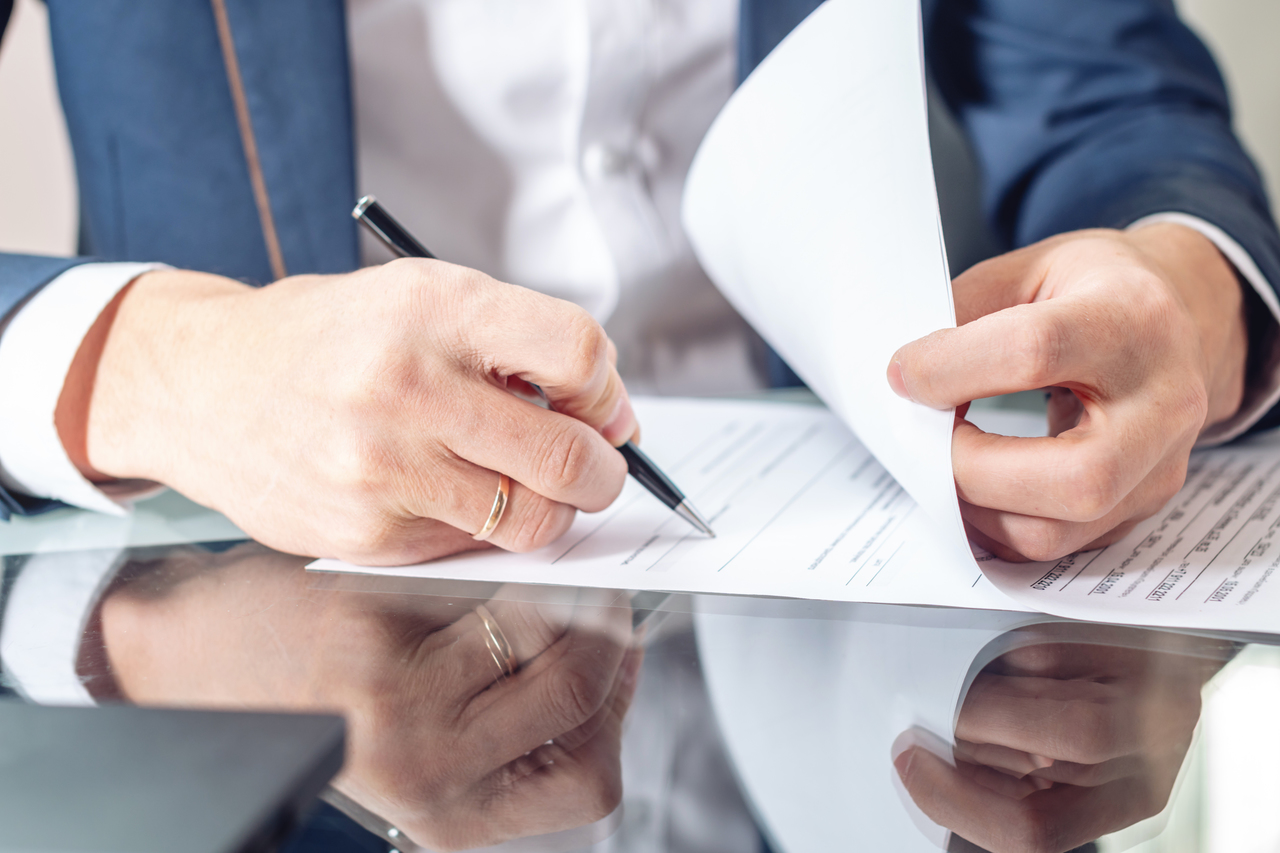 Businessman sitting at the table signing documents in the office close up