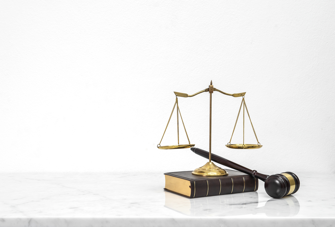Wooden gavel and law book put on white marble table top counter with copy space.