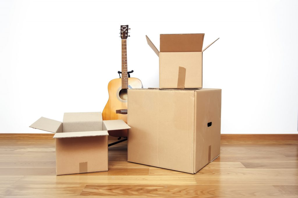 Open cardboard boxes with guitar on the floor in empty room, ready for transport