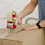 man packing box with tape