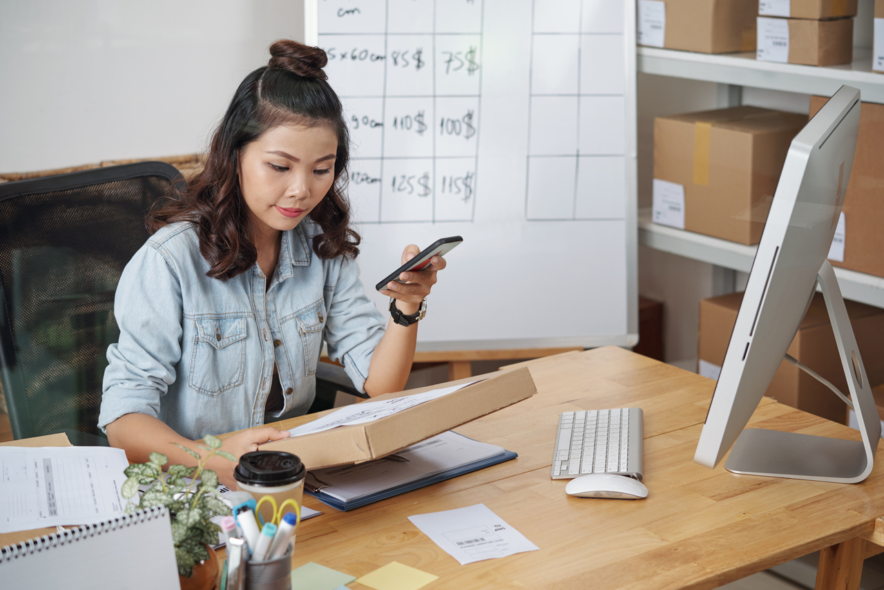 Asian young woman reading address on packed box and talking on cell phone