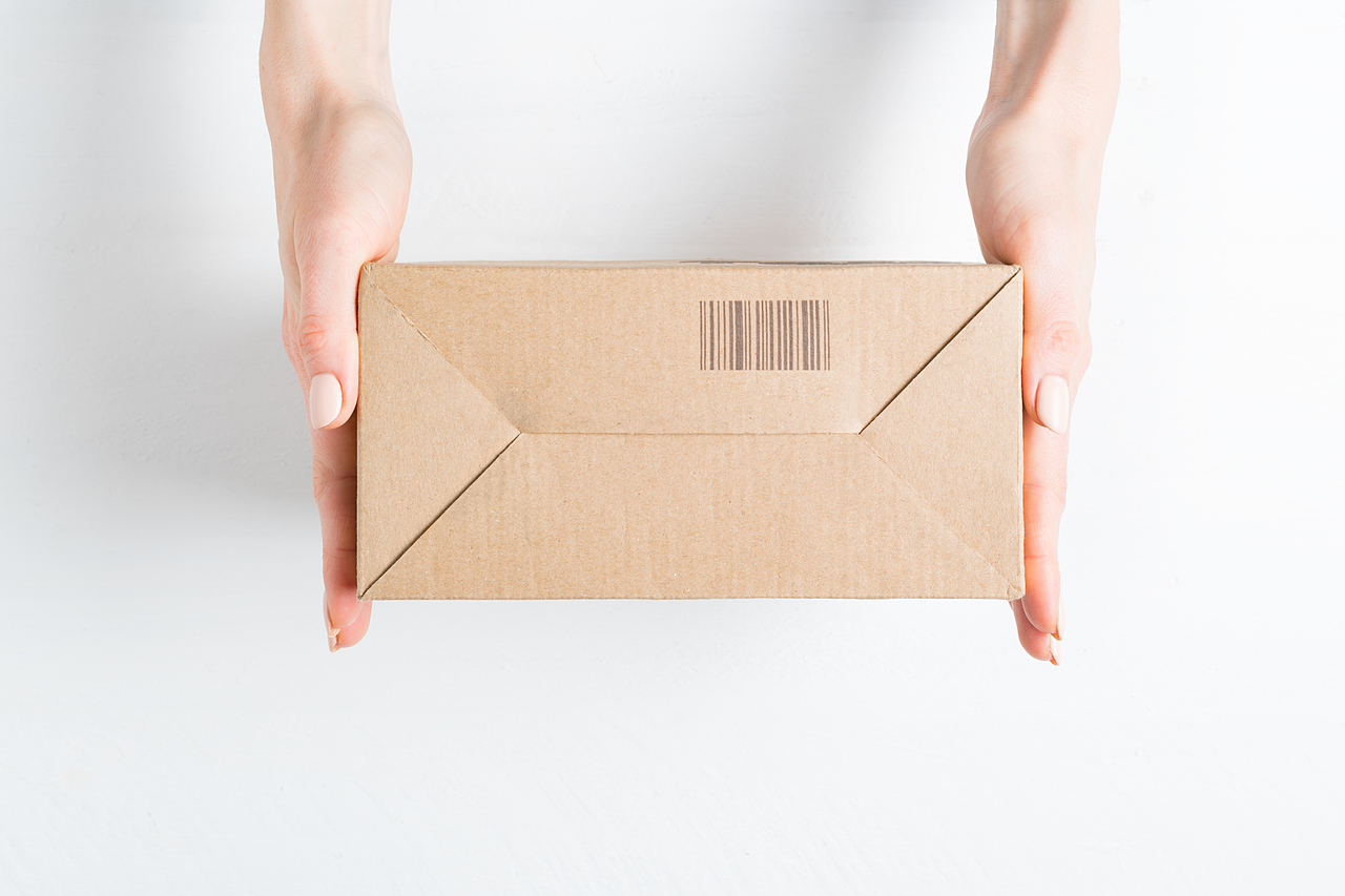 Rectangular cardboard box with barcode in female hands. Top view, white background