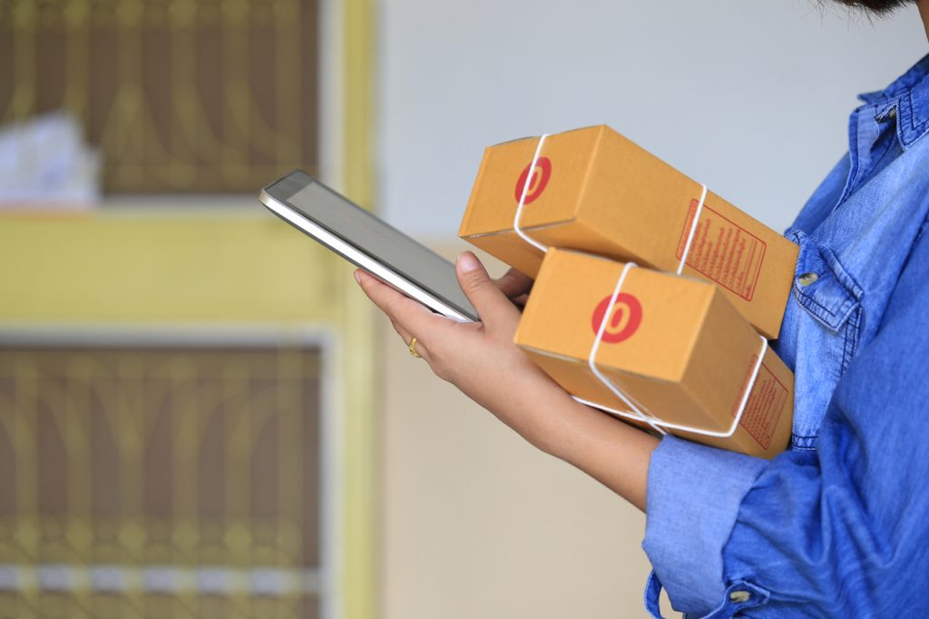 Online shopping, Woman hand holding smart phone and tracking parcel online to update status with hologram, Ecommerce and delivery service status tracking concept
