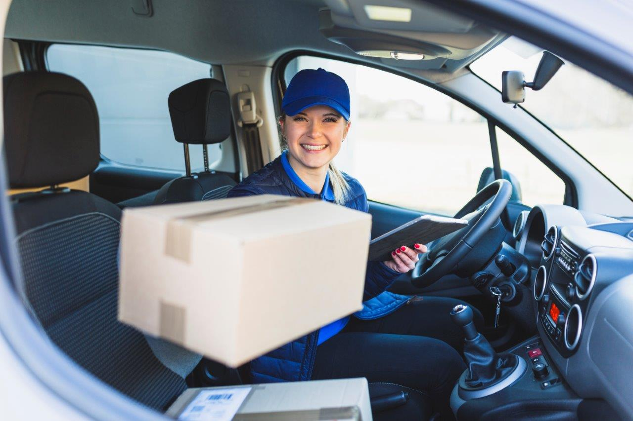 woman in van handing package