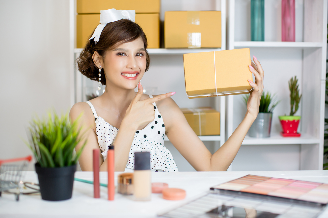 Asian girl working at home office and sorting parcel post box