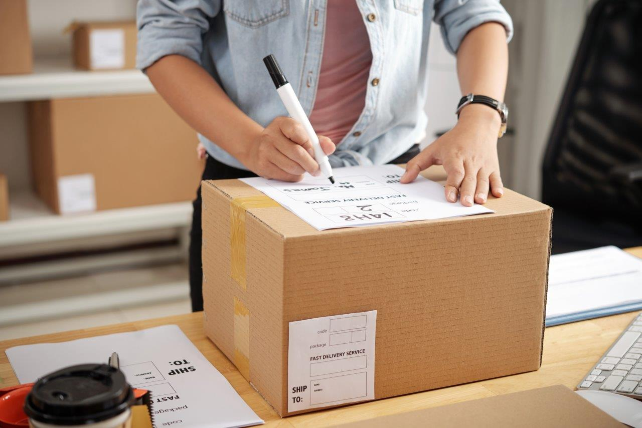 woman writing label on box