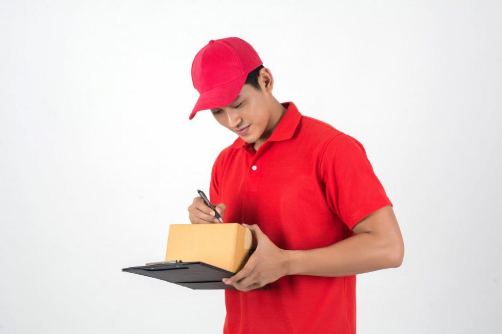 man in red shirt signing package