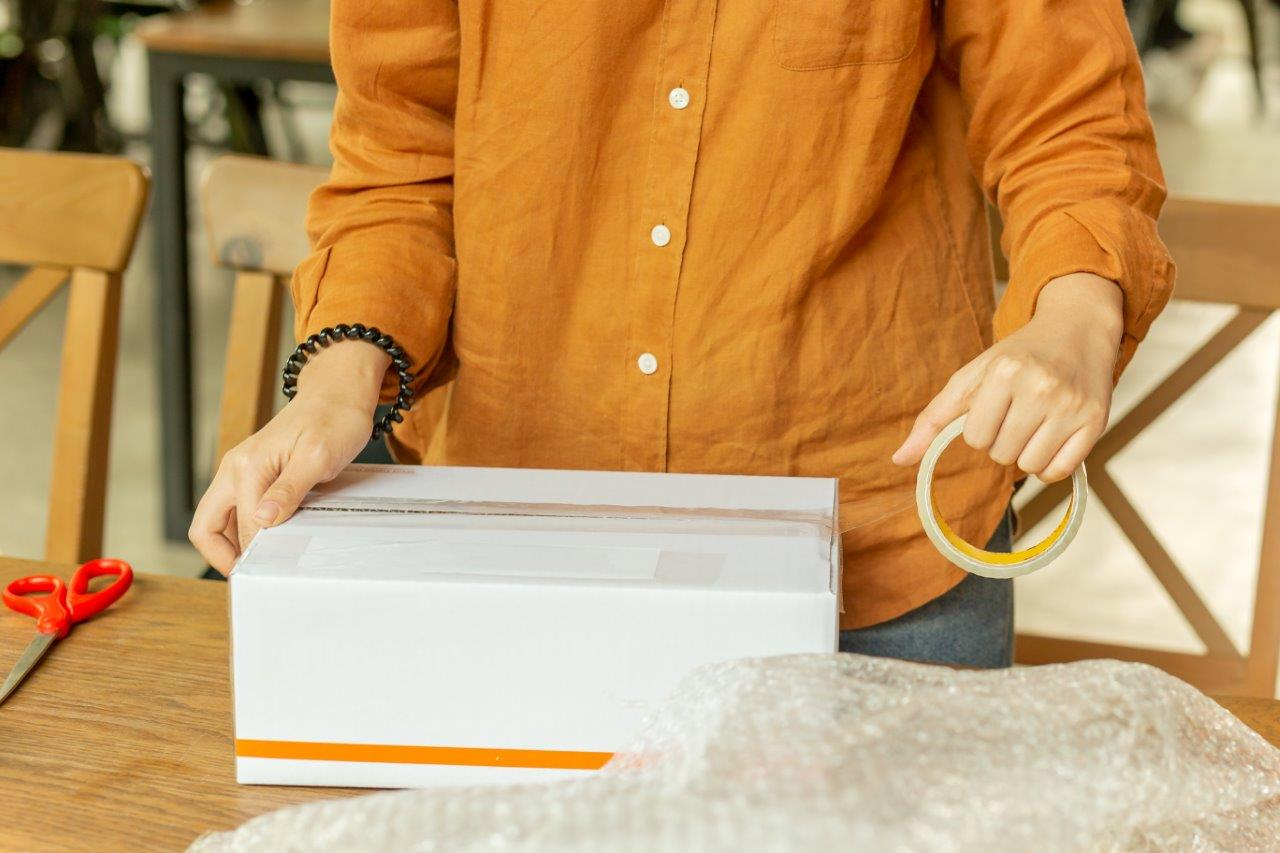woman packing box using bubble wrap