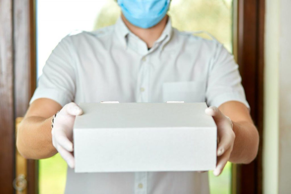 man wearing gloves and mask holding out package