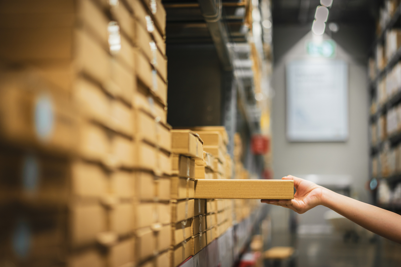 A woman picking a box out of a warehouse