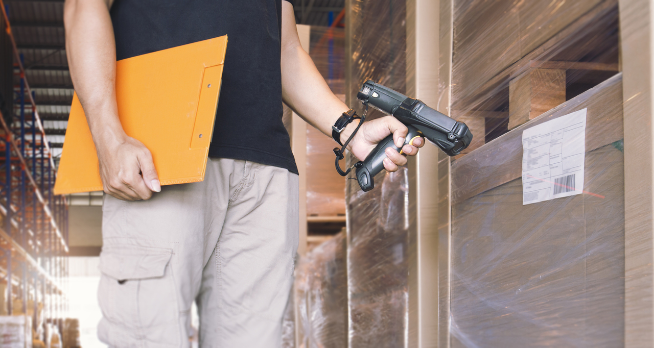 A man scanning a package for a tracking system