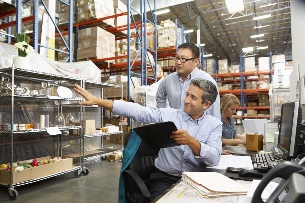 Business Colleagues Working At Desk In Warehouse