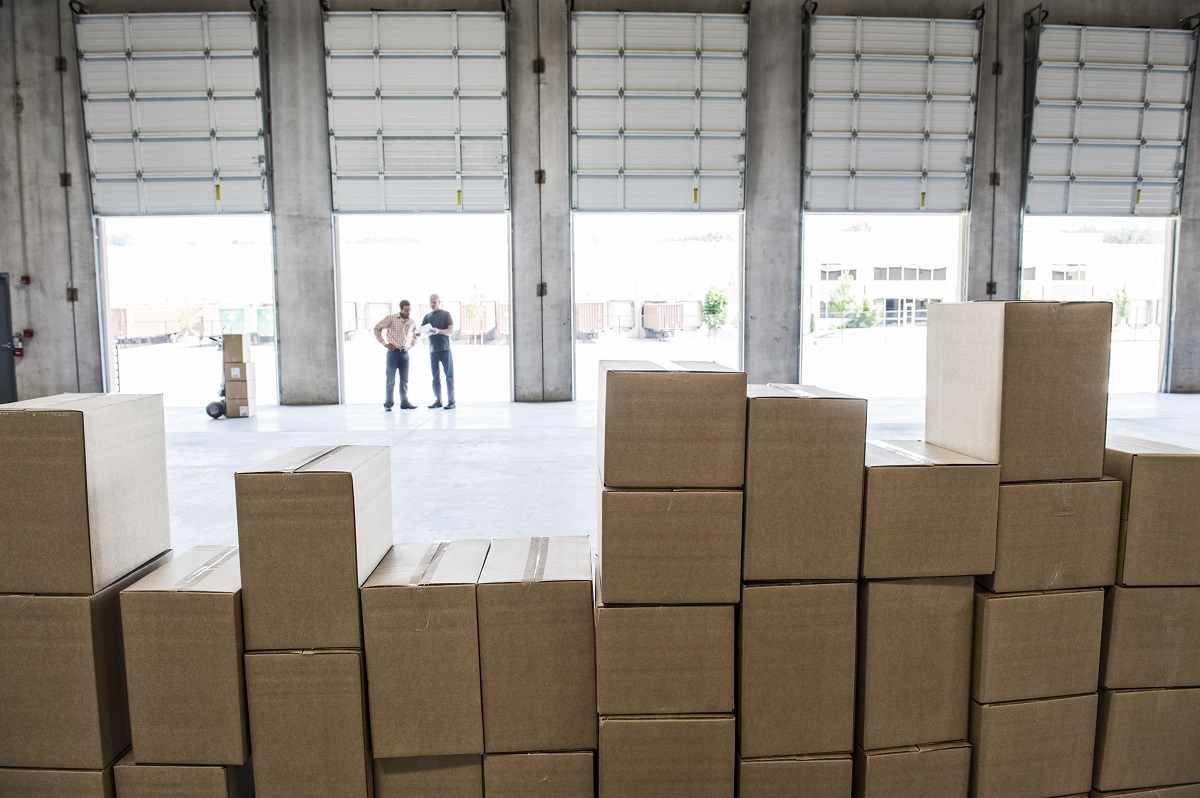 Team of workers check out inventory in front of loading dock doors in a new warehouse.