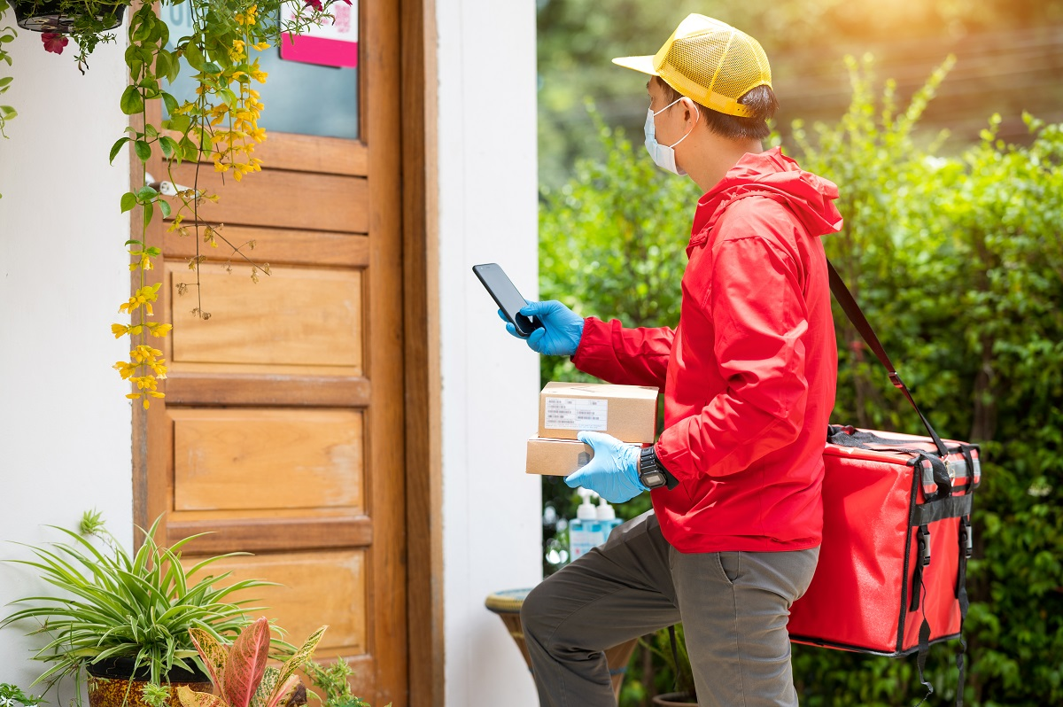 delivery man Wearing blue gloves in red cloth Searching for customer address by mobile phone