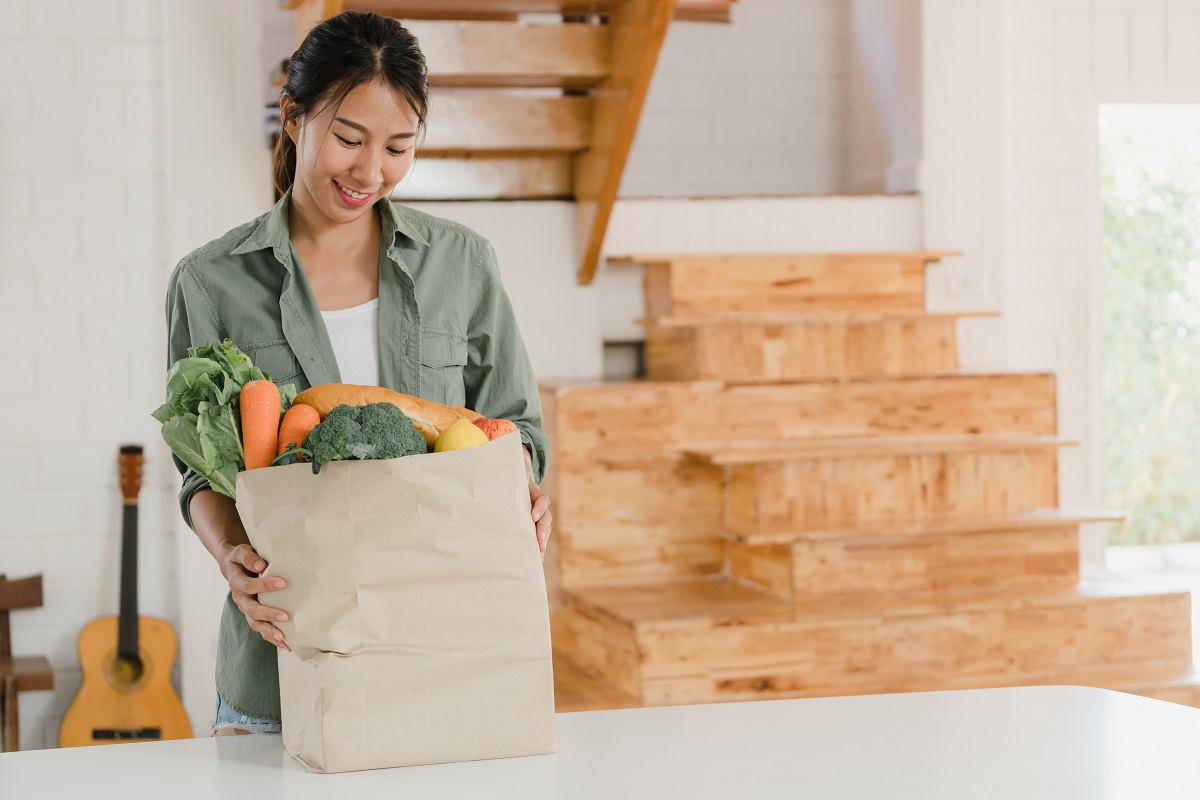 Asian women holding grocery shopping paper bags at home, young A