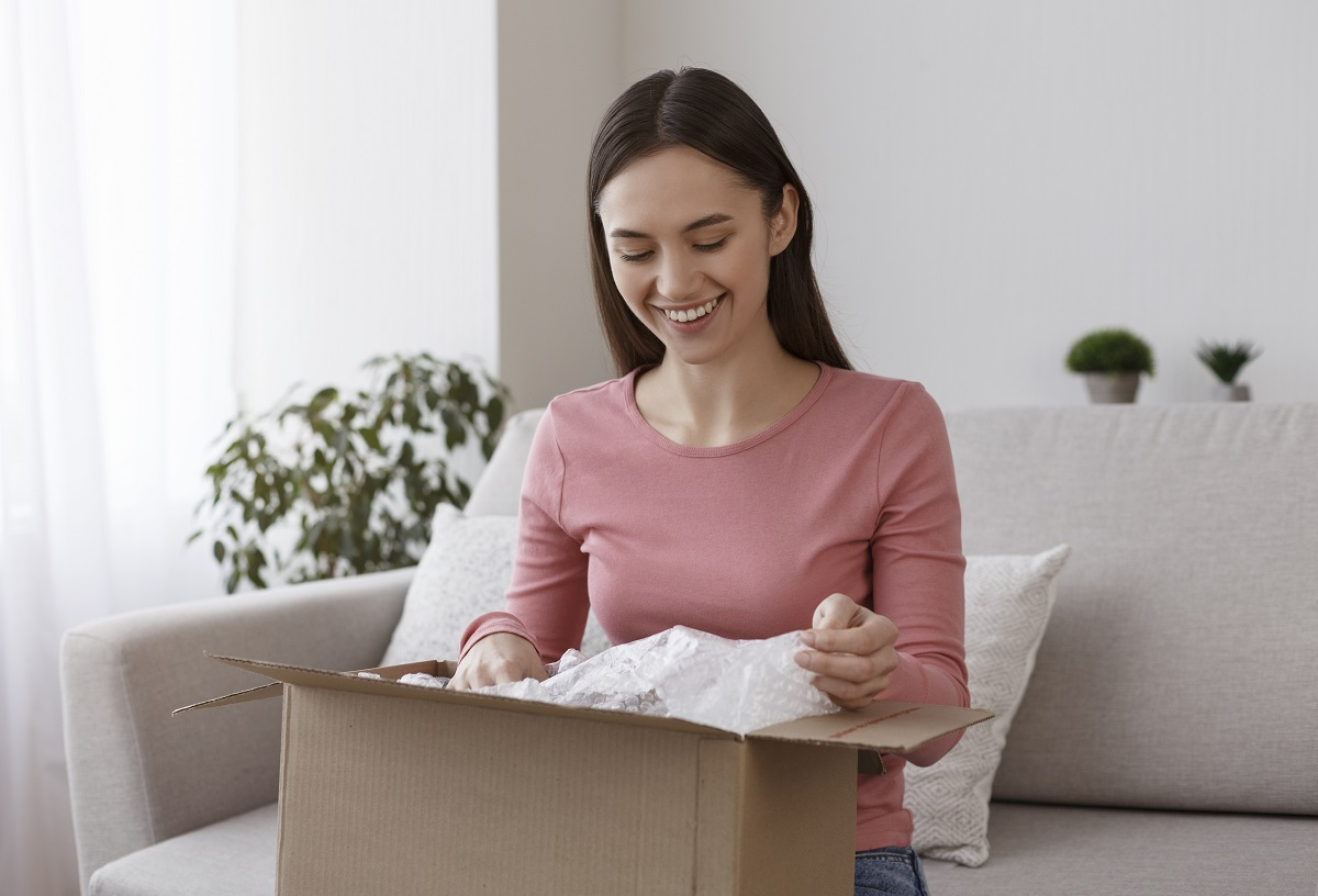 Happy young girl unboxing international package at home