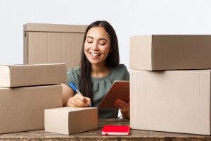 Small business owners, startup and e-commerce concept. Smiling successful asian businesswoman with own internet shop, selling online, writing shipping info on boxes with customer orders, use tablet